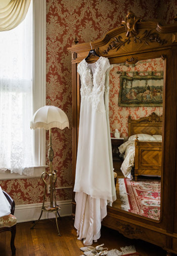 white wedding dress hanging from the armoire in the Master Chamber with the reflection of the bed in the mirror