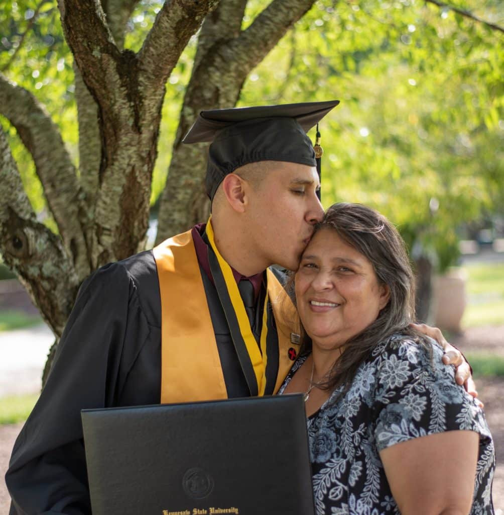 Tall male, Latino, kissing shorter mom on side of forehead as he holds degree folder