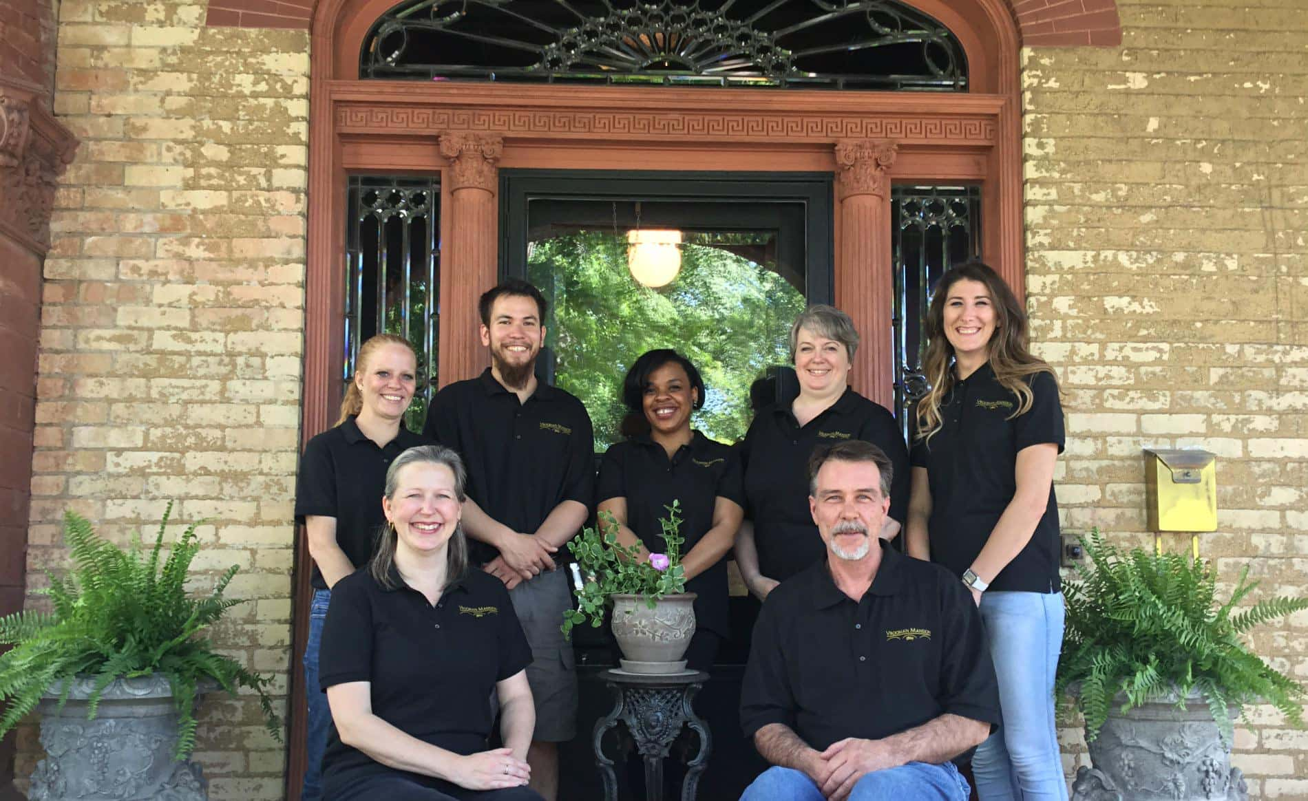 Two men and five women wearing black polo shirts in front of an elaborate leaded glass front door