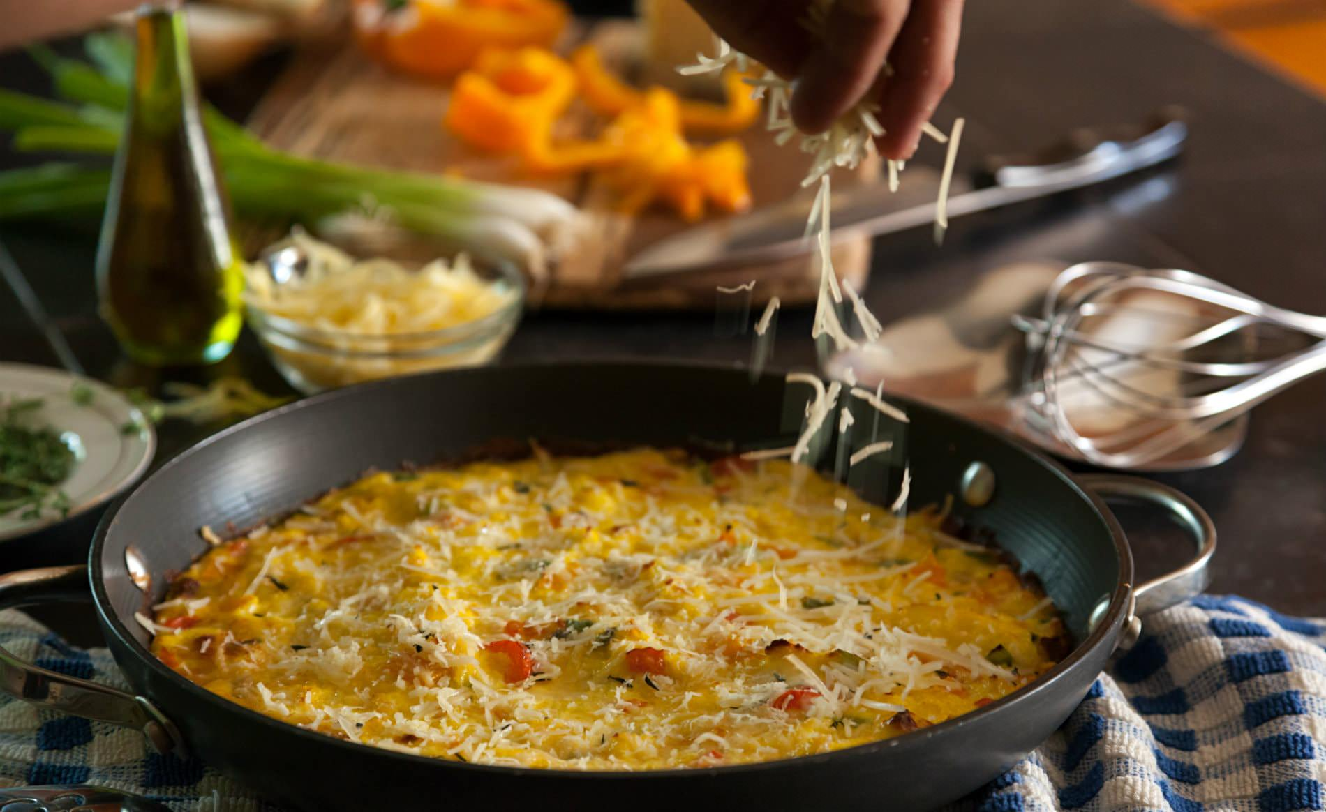 Close up view of a chef cooking an omelet with chopped veggies and herbs and shredded cheese nearby