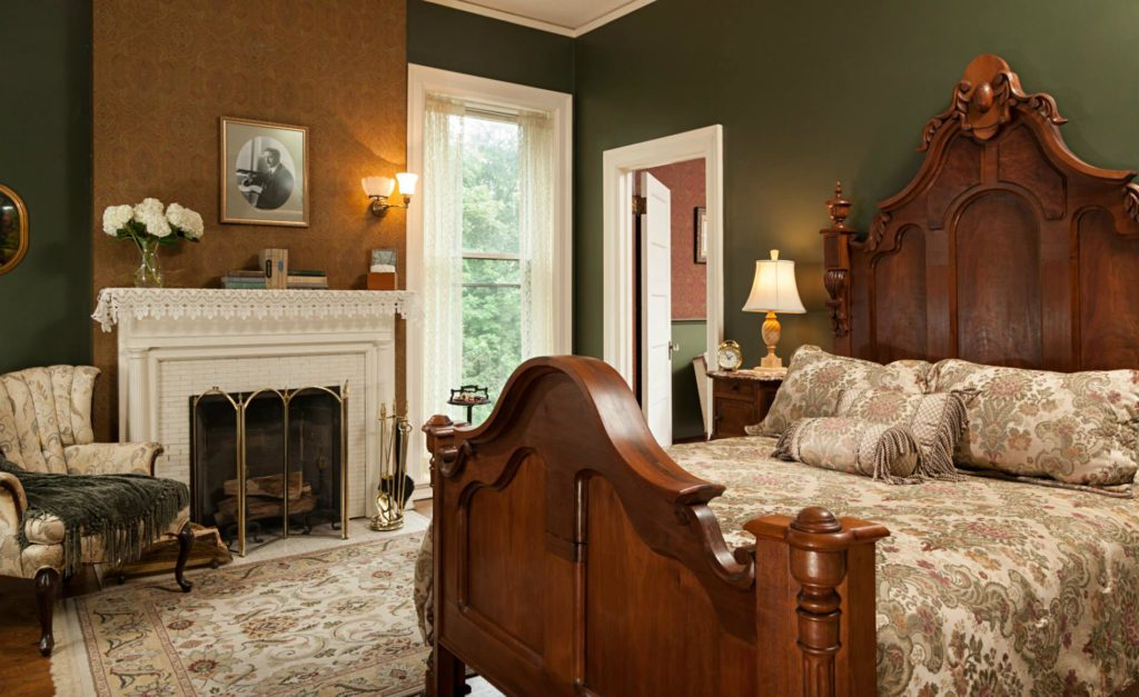 Deep green room with white trim and doors, wood floors, fireplace, and large elegant wood bed with floral bedding