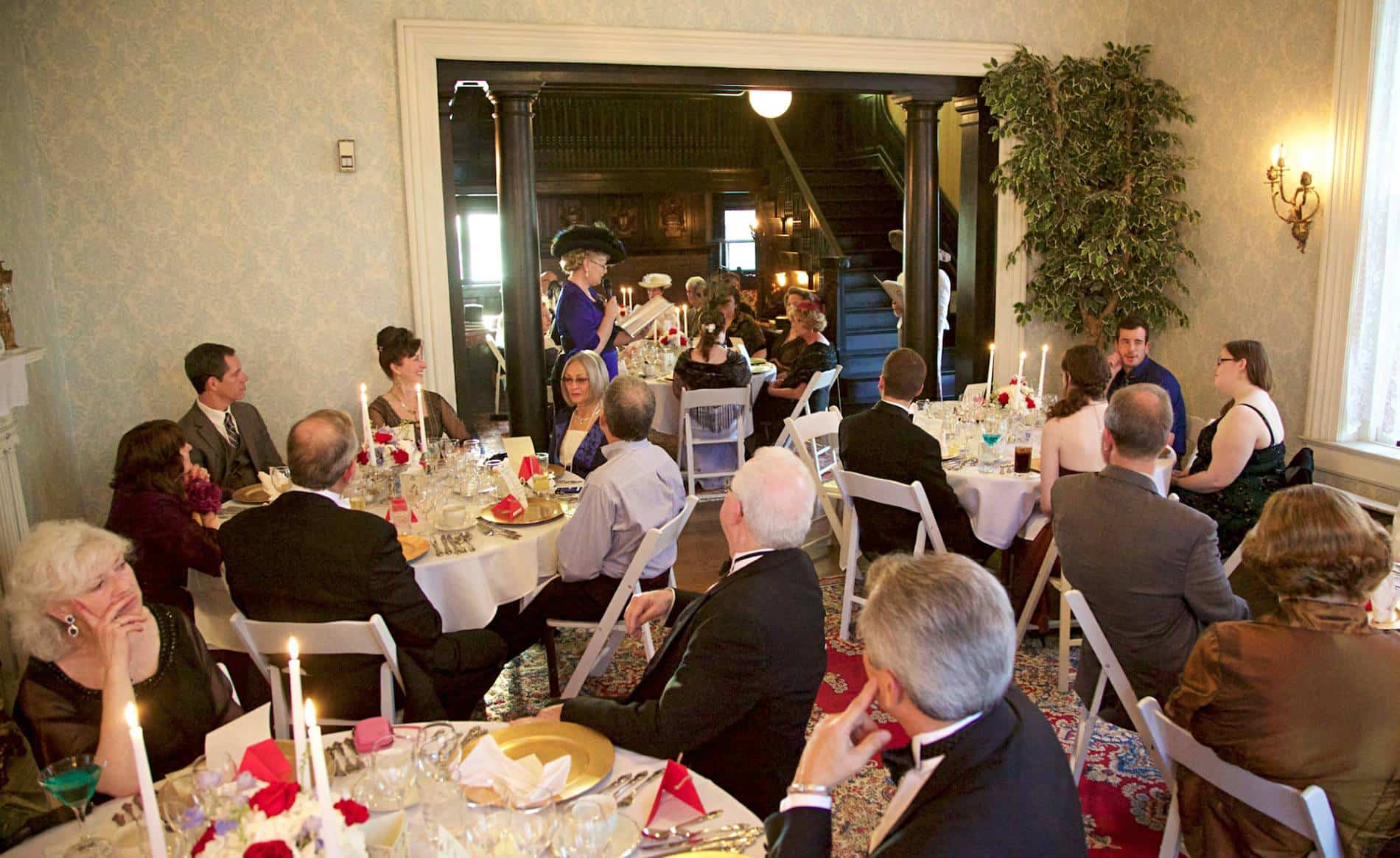 Large group of well-dressed people sitting at white tables set for a meal