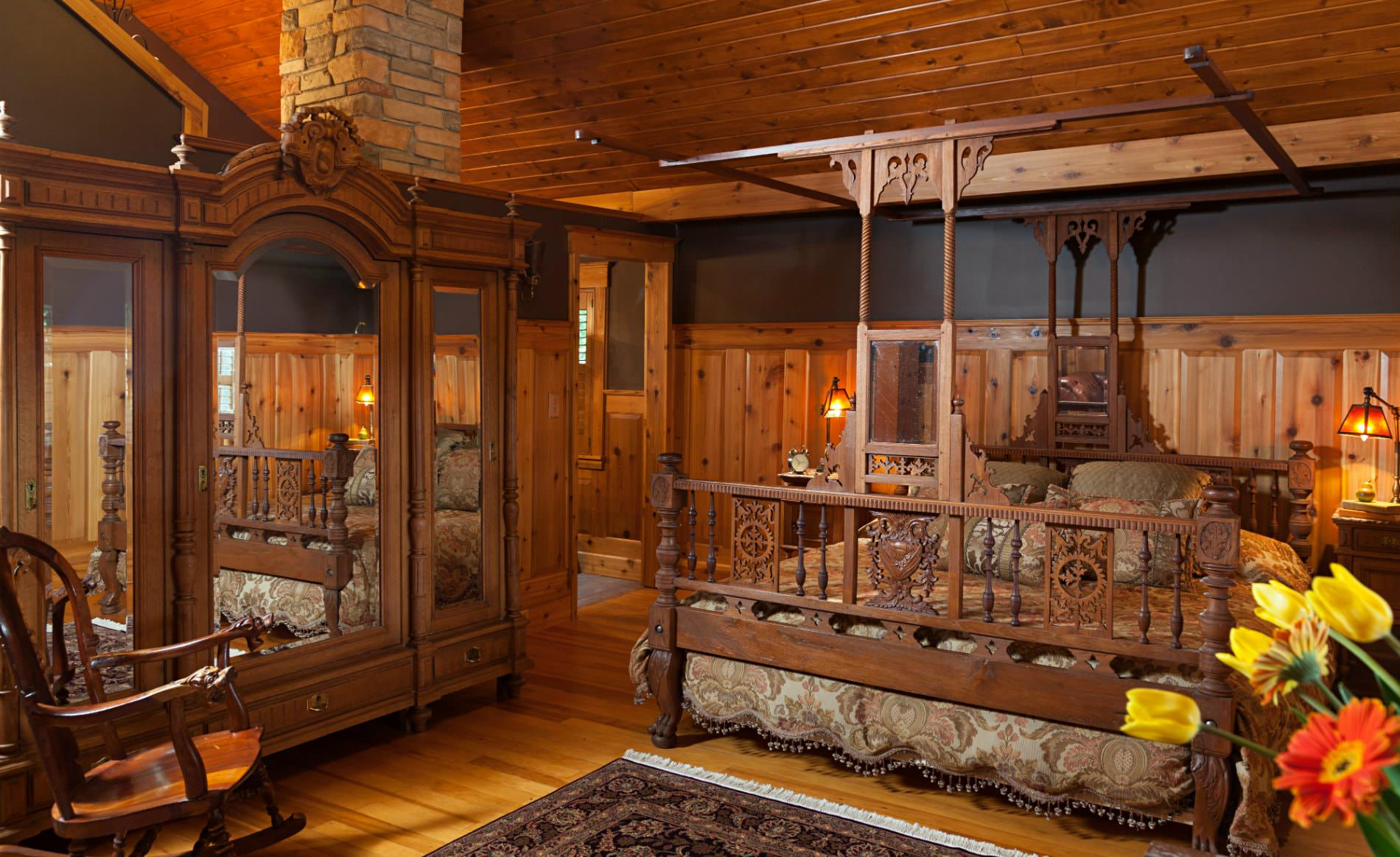 Rustic room with pine ceiling, walls and floor, elaborately carved king sized bed, and mirrored cabinet with triple doors