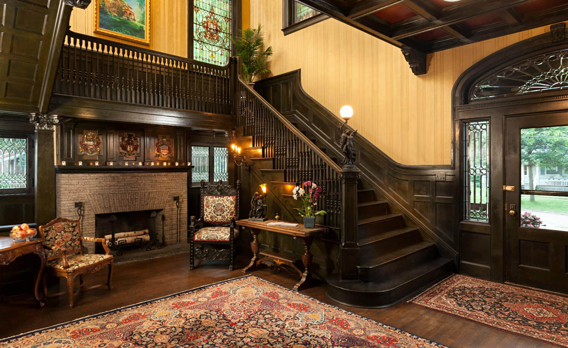 Beige papered walls, wood floors, ornamental rug, two side chairs flanking a fireplace and an elaborate dark wood staircase