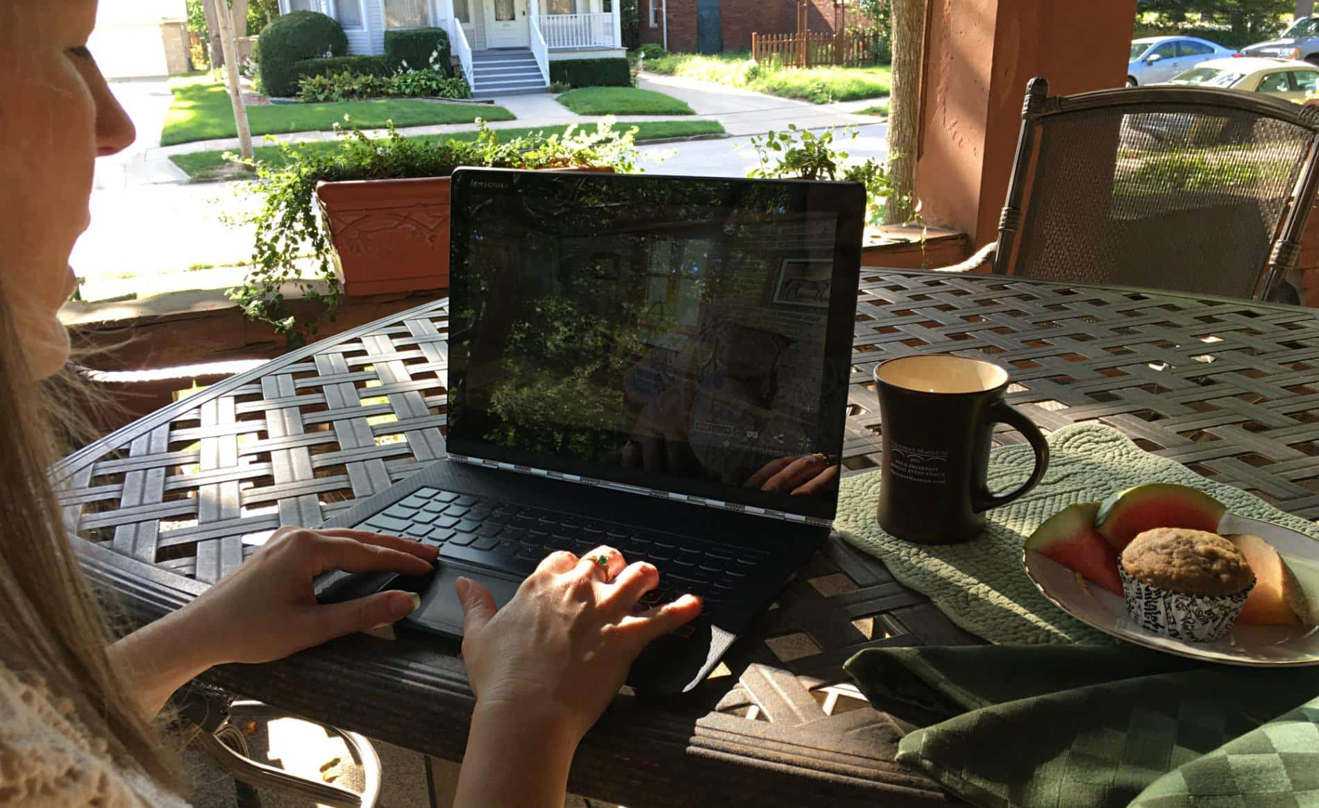 Woman sitting at a black patio table typing on her laptop with a mug, fresh melon and a muffin nearby