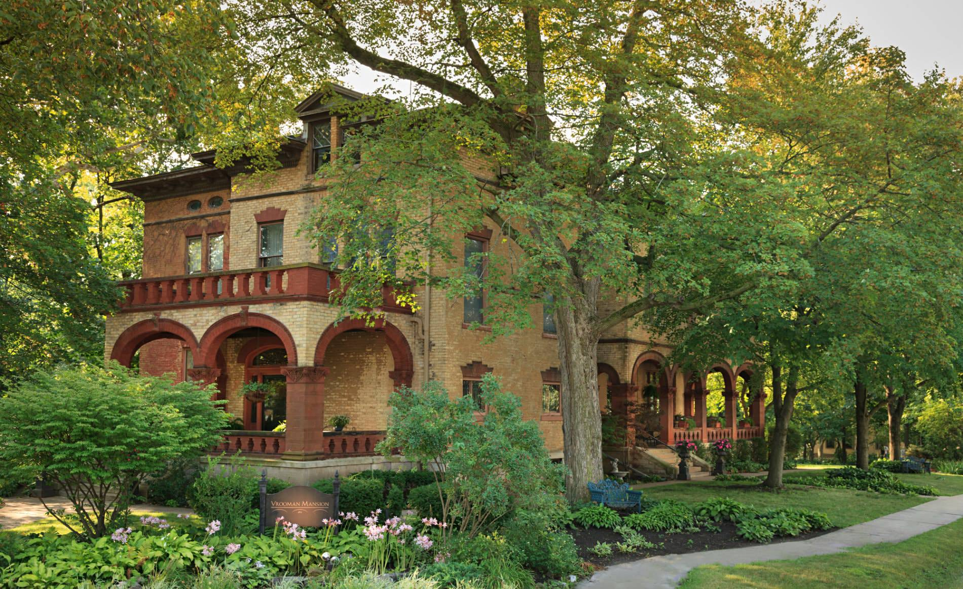 Vrooman mansion with arched covered porches and arch windows and doors surrounded by green plants, grass and trees