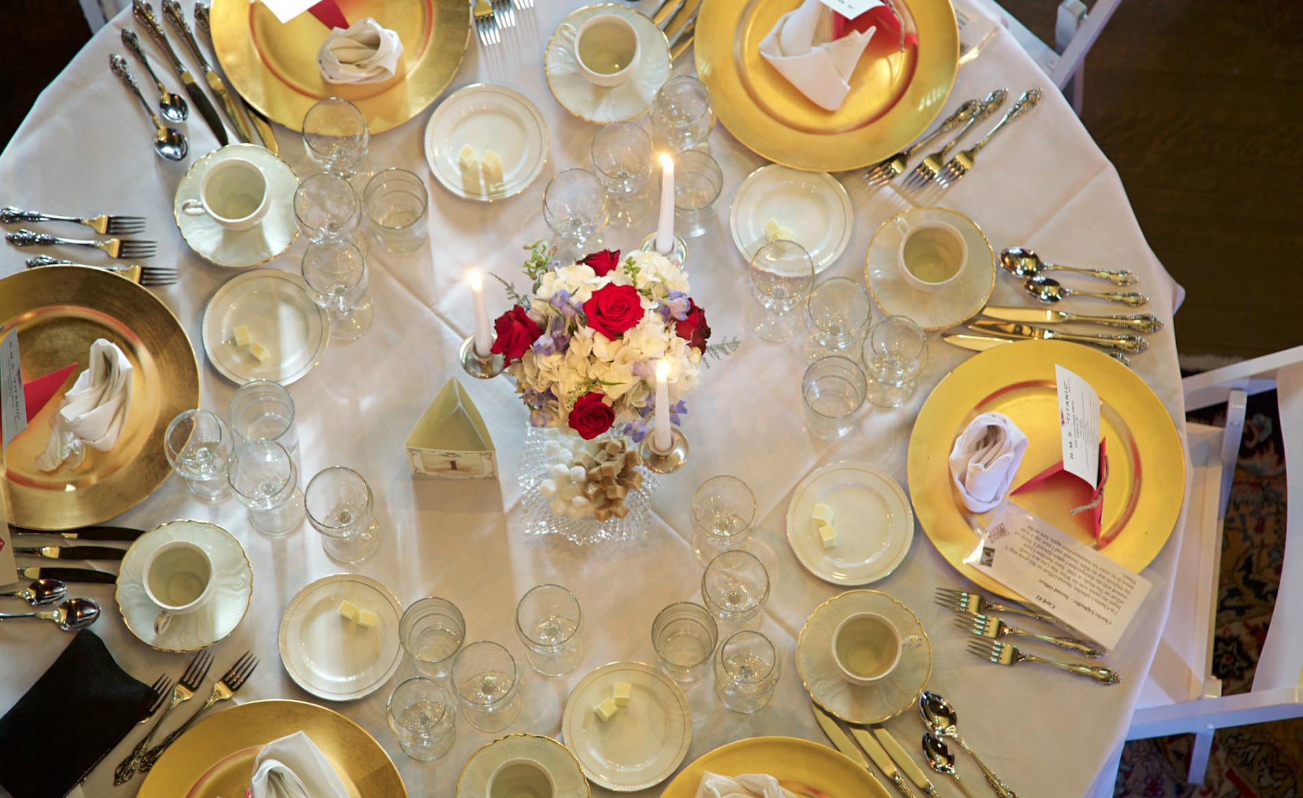 White covered table set with gold and white dishes, wine glasses, and three white lite candles around a floral centerpiece
