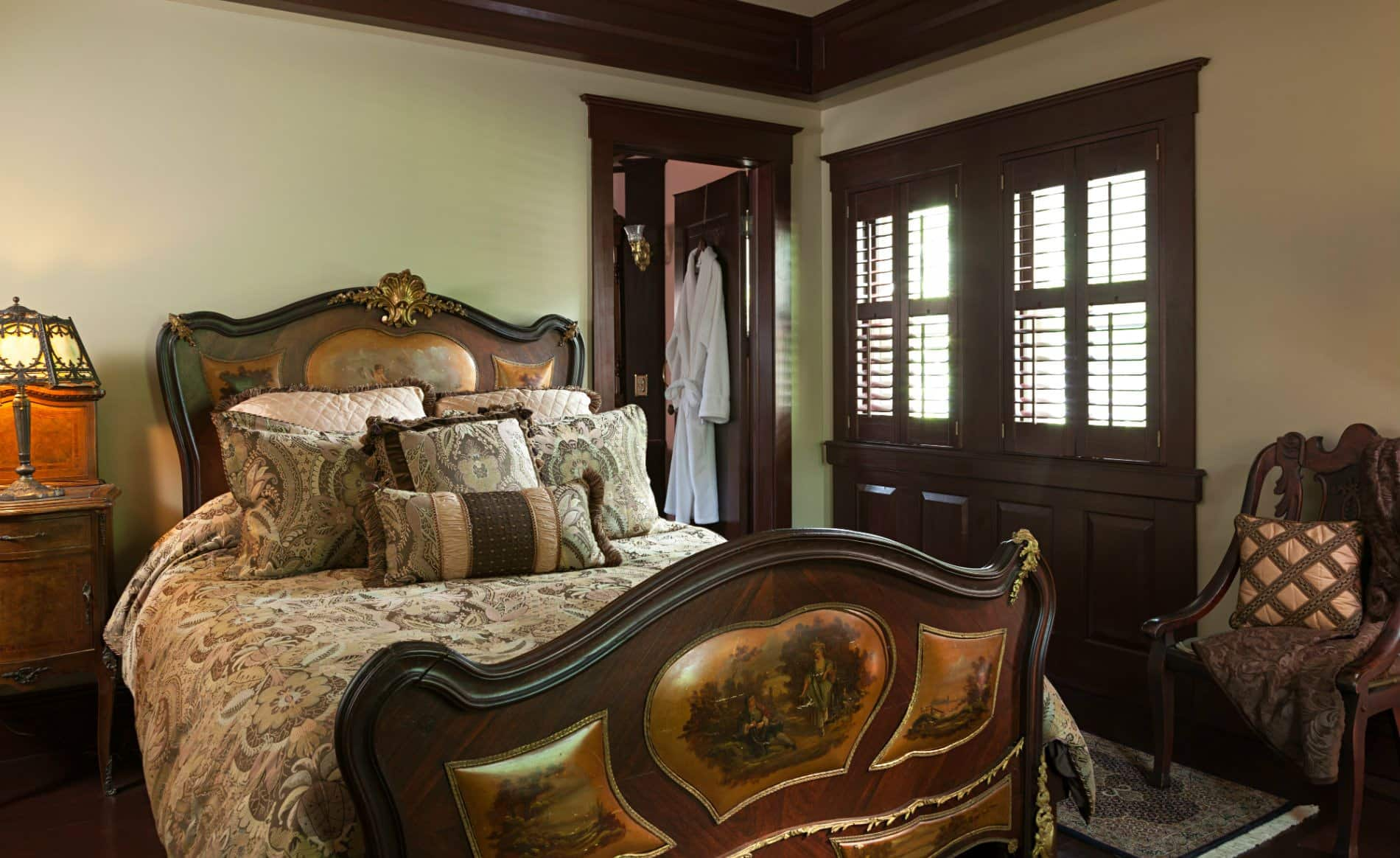Beige room with dark stained trim and doors, wood floors, elaborate bed and a nightstand with antique lamp
