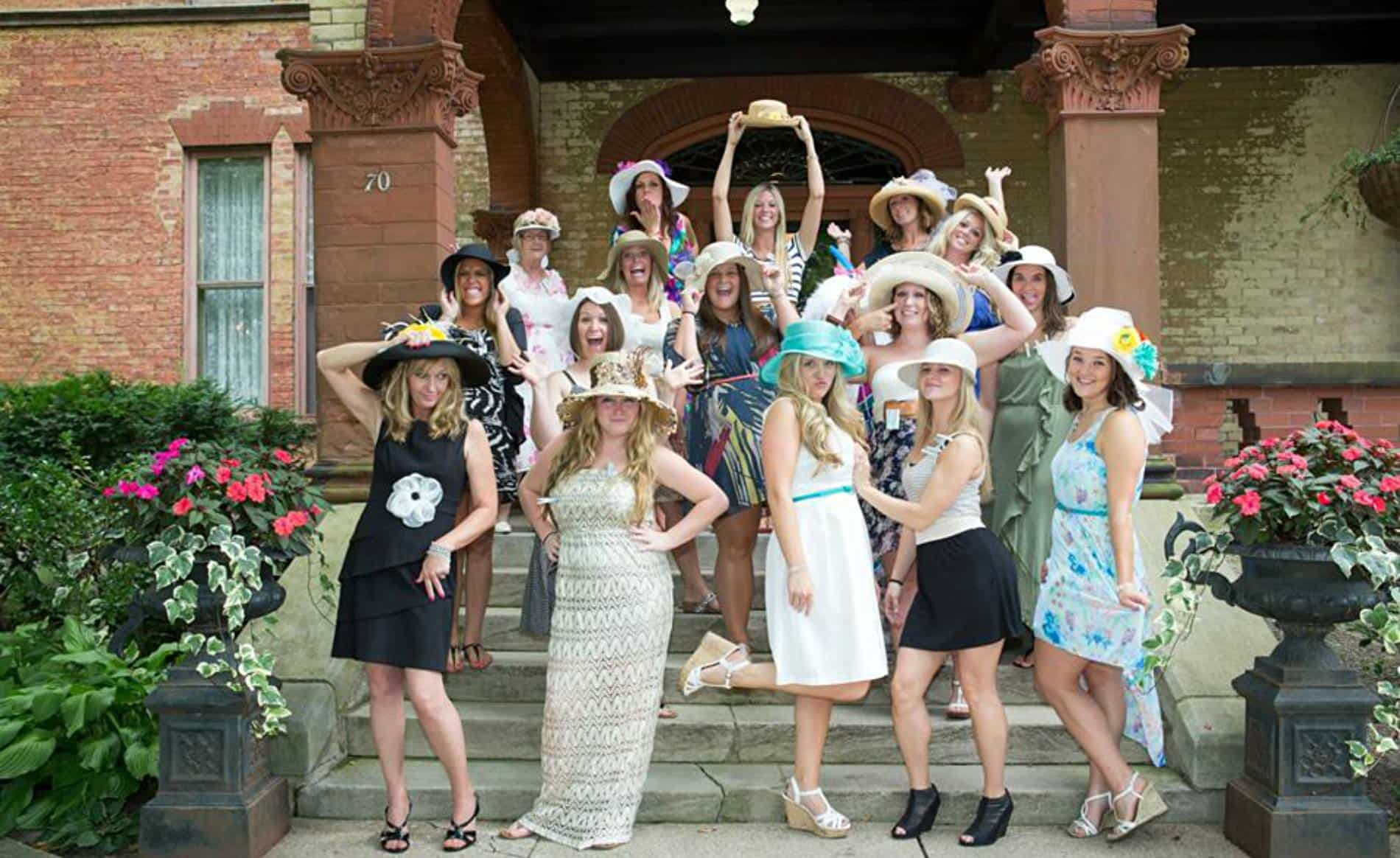 Group of women wearing colorful dresses and hats posing on the concrete steps leading up to the front door
