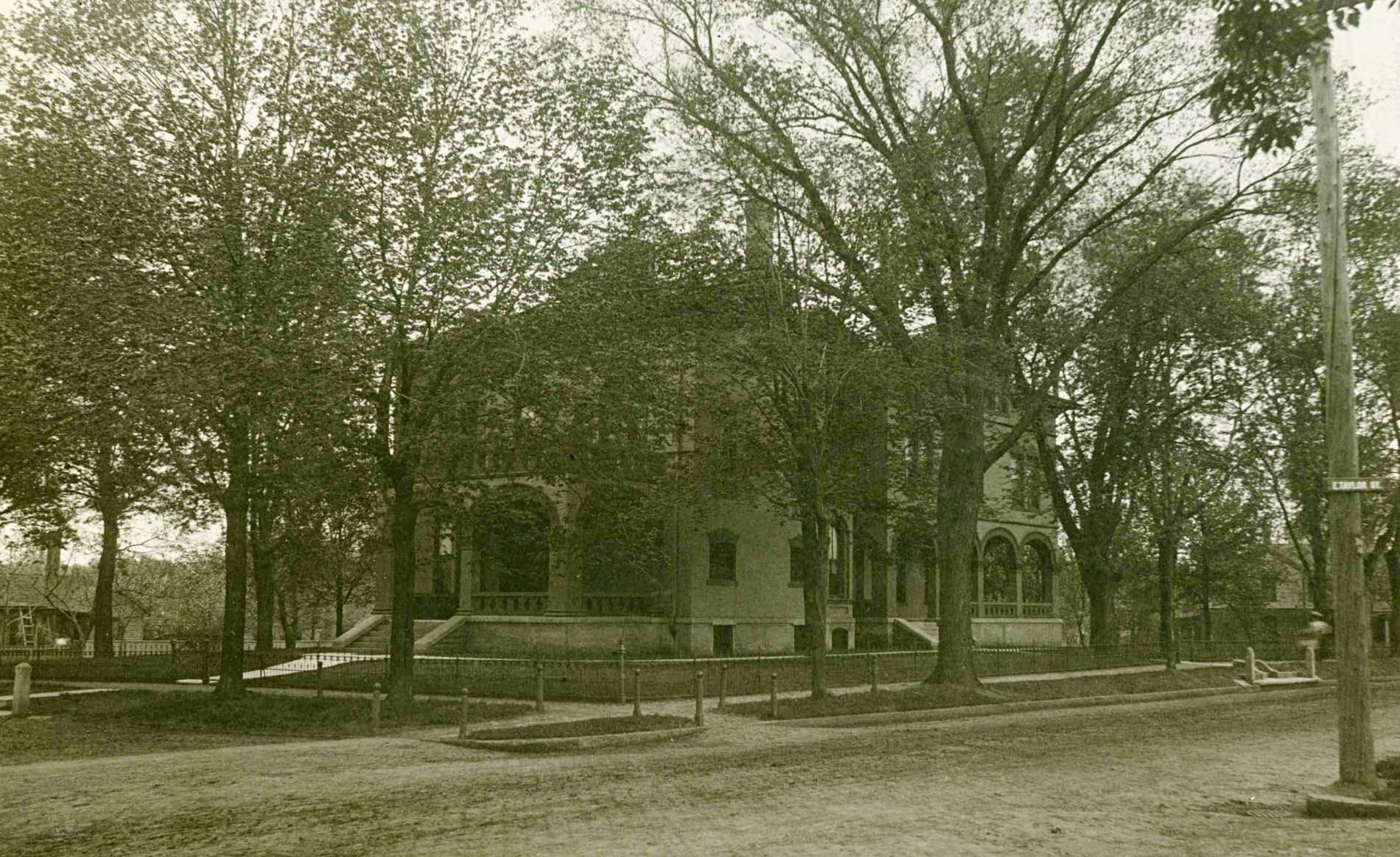 Black and white photo of the Vrooman mansion with arched windows and doors surrounded by trees