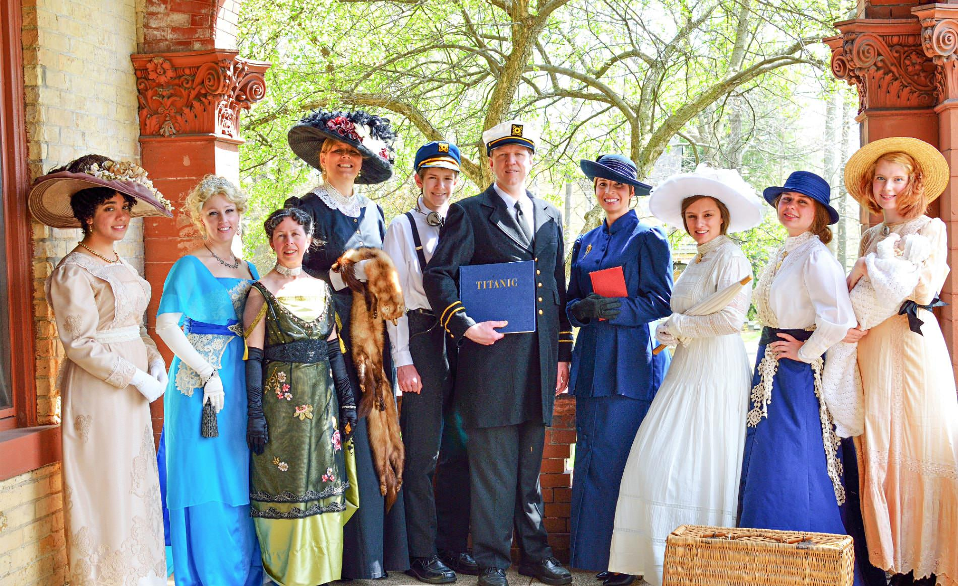 Group of people standing on the covered porch wearing old-fashioned elegant clothing in blues, whites and other colors