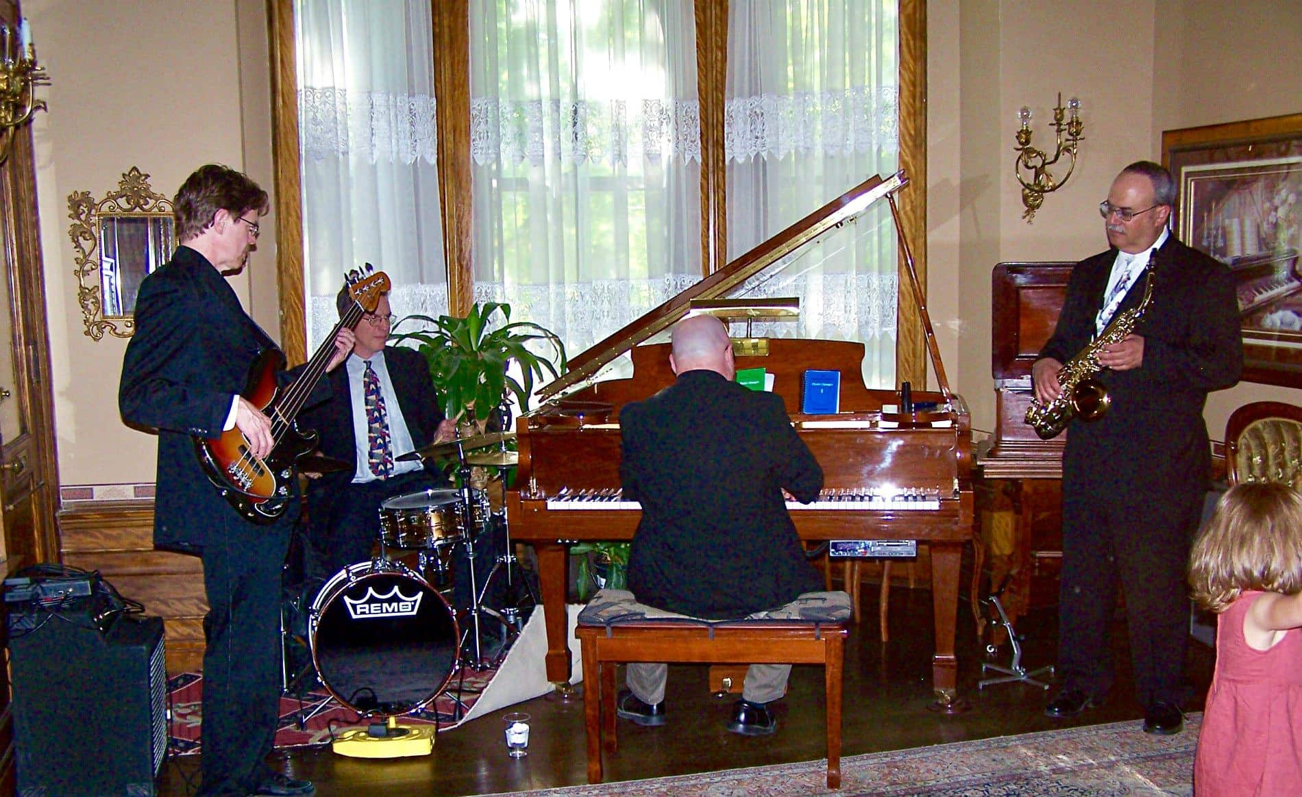 Four men in dark blue suits playing guitar, piano, drums and saxophone