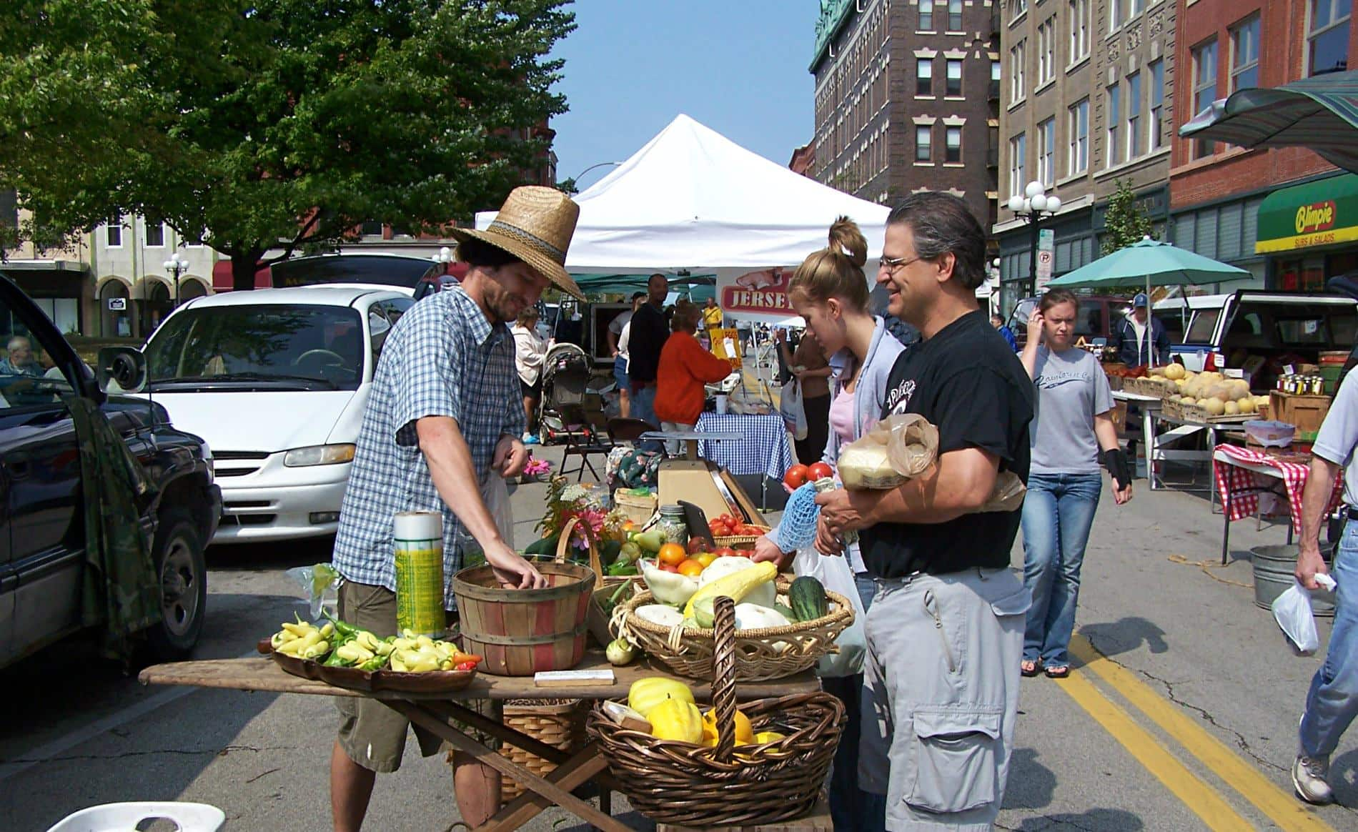 Outdoor farmers market in the street with vendors selling fresh produce to customers amidst buildings, cars, trees and blue skies
