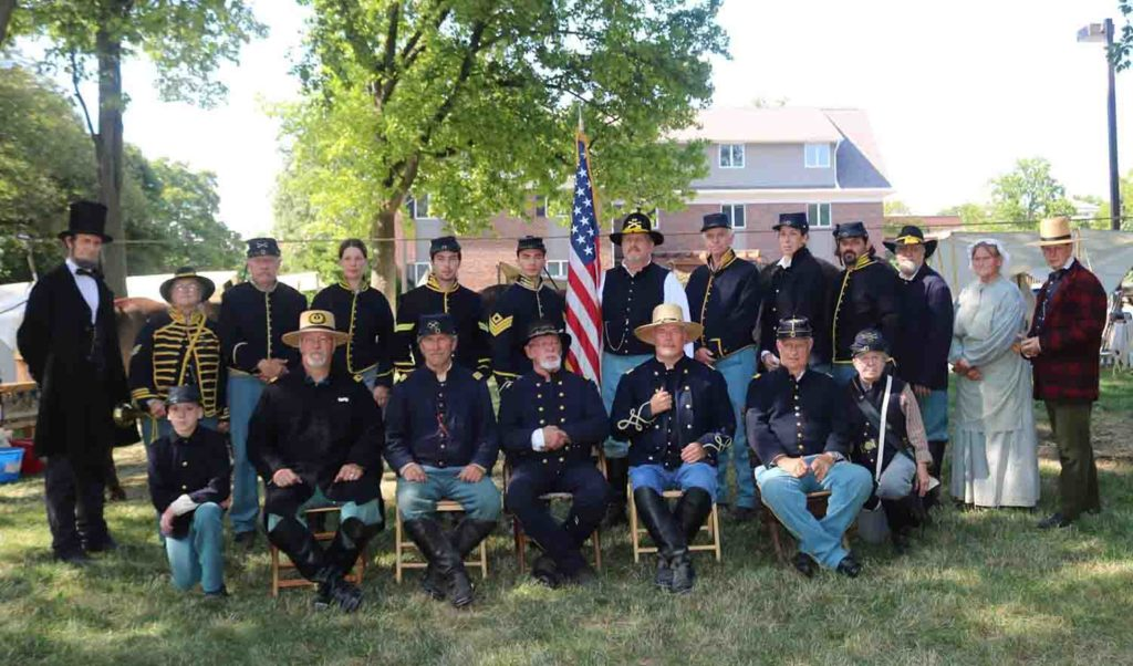 Men dressed in navy blue Civil War uniforms sitting together in a grassy shaded park