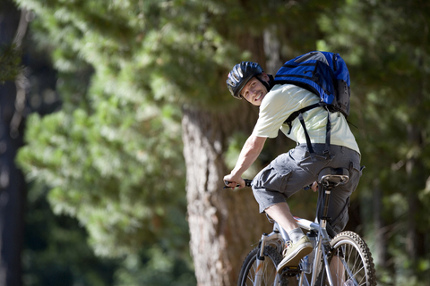 Man weargin a backpack and riding a bicycle