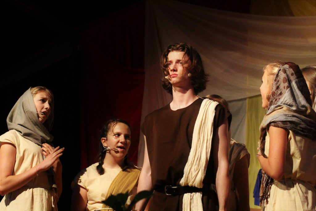 Three teen girls around 1 teen boy in brown and beige toga or biblical times costumes, performing.