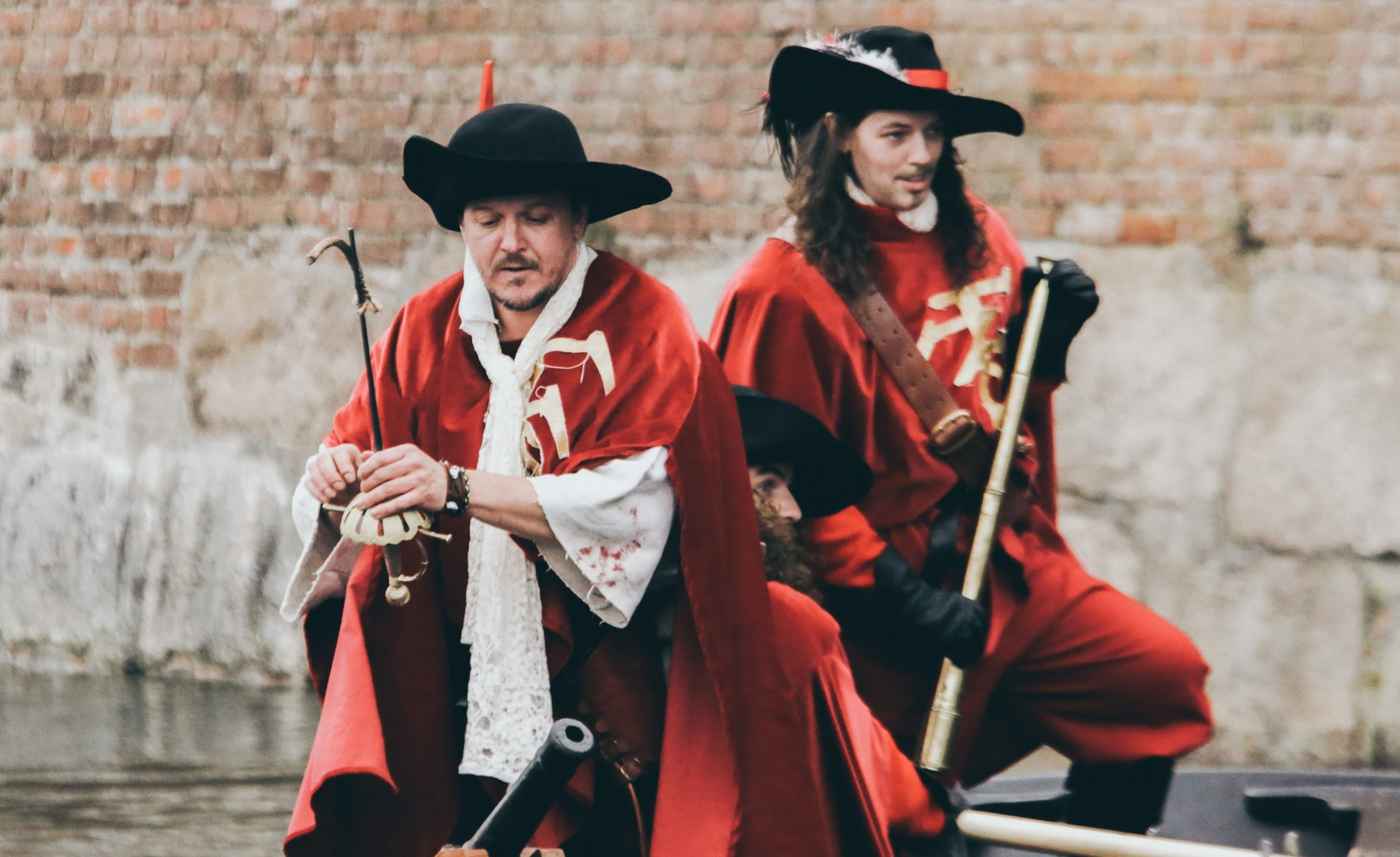 Two men in red and black costumes like 3 Muskateers, sitting and learning in front of brick wall.