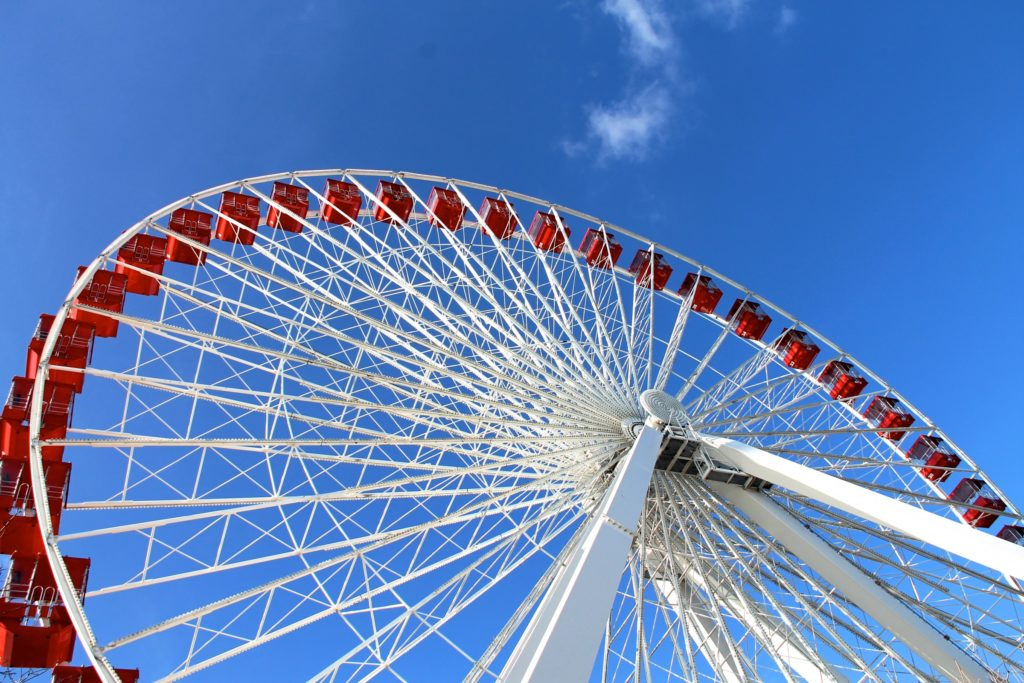 Looking up at a red and white ferris wheel amidst bright blue skies