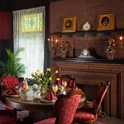 Elegant dining room with red velvet chairs, lace covered window and elaborate brick fireplace