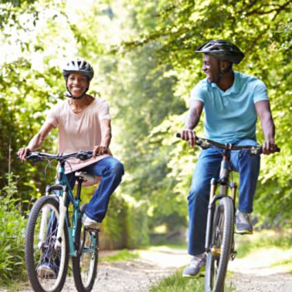Man in blue shirt and woman in pink shirt wearing bike helmets while riding bicycles on a tree-lined path