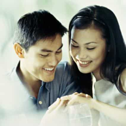 Black haired man and woman smiling while looking at women's engagement ring