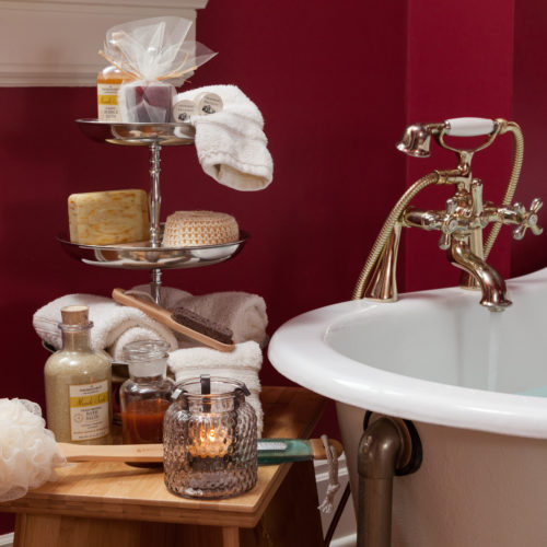 Basket of white towels, rolled up ivory towel, cinnamon sticks, bottles of cream, jar of oil and sea salt