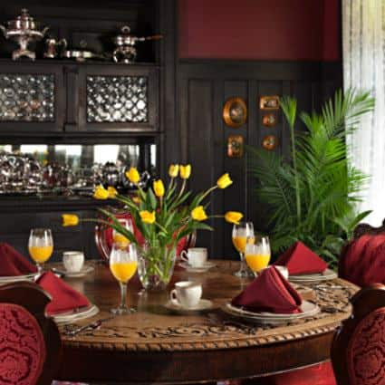Red velvet chairs and carved wood table set with red napkins and white china and wine glasses of orange juice