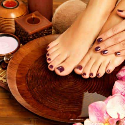 Woman's feet and left hand freshly manicured with dark red polish