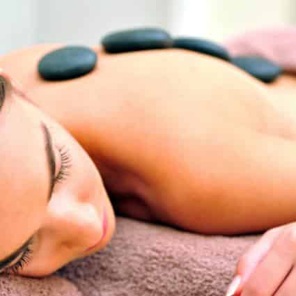 Woman face down on massage table with eyes closed and dark gray stones on her back