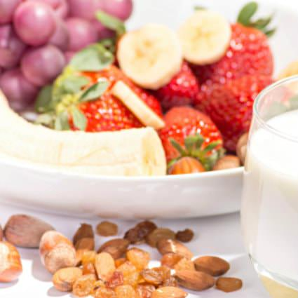 Close up view of white bowl filled with fresh fruit, glass of milk and assorted nuts