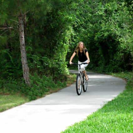 Long-haired woman riding a bicycle down a concrete path surrounded by lush green grass and trees