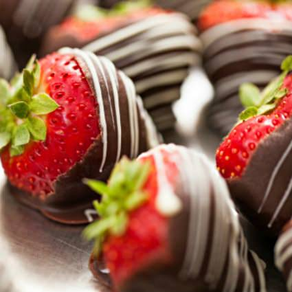 Close up view of fresh red strawberries with green stems covered in white drizzled dark chocolate
