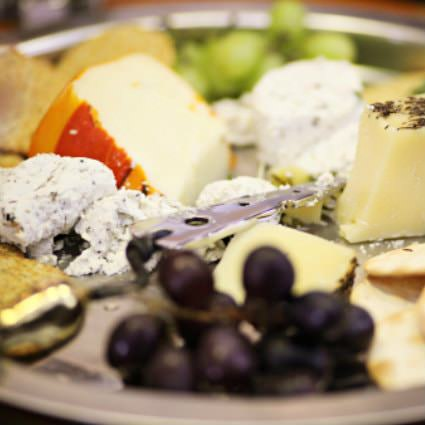 close up view white plate topped with various cheese and grapes