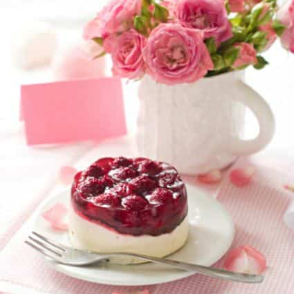 Pink and white tablecloth, white plate of raspberry dessert, white mug of pink carnations, and pink place card