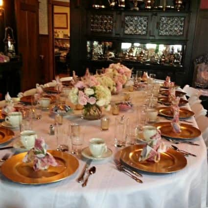 White covered oval table set for dinner with gold plates, white cups and saucers and pastel floral centerpieces