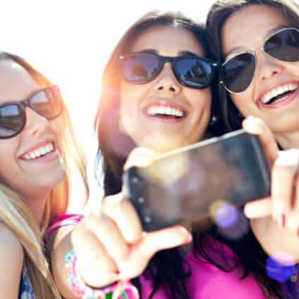 Close up view of three young women smiling, wearing sunglasses, while taking a selfie with a smart phone