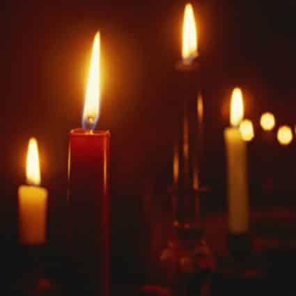 Close-up view of red and white lit candles in a dark room
