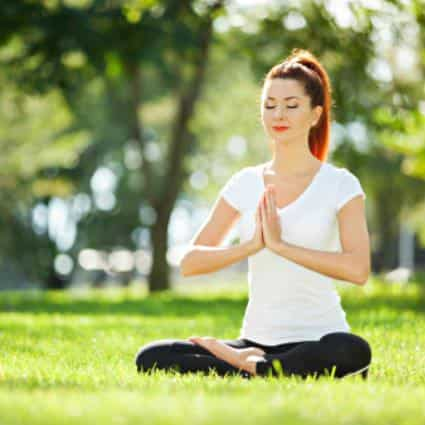 Dark-haired woman with pony tail, white shirt and black leggings sitting in the grass meditating with her eyes closed