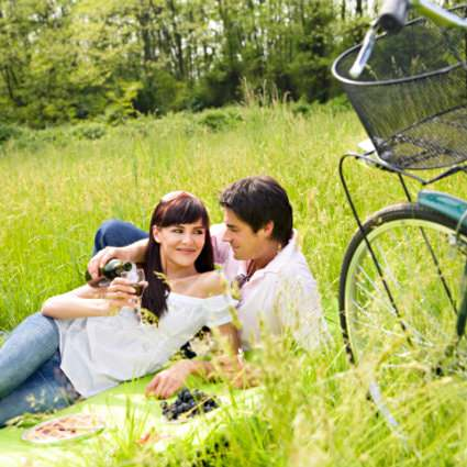 Man and woman laying on a picnic blanket in the green grass sipping red wine