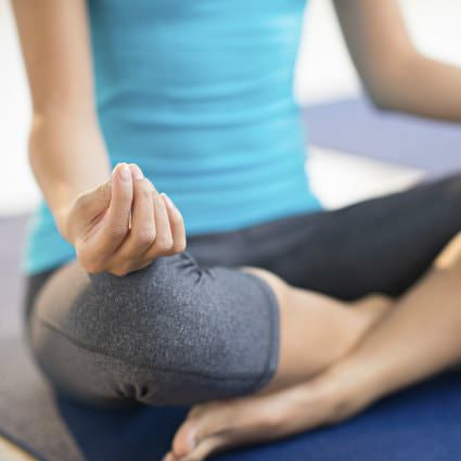 Woman's body wearing a blue shirt, grey leggings sitting cross-legged on a blue mat in a yoga position