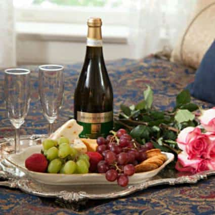 Silver platter topped with champagne, two flutes, fresh roses and white bowl of fresh fruit