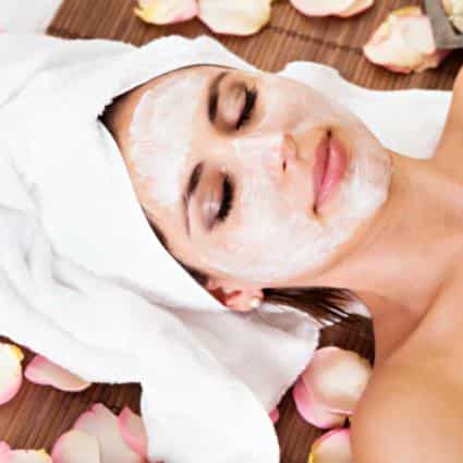 Woman laying with eyes closed, white towel on her head and face covered with white cream surrounded by rose petals