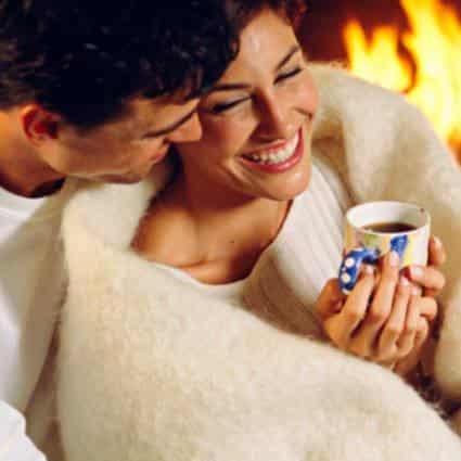 Man embracing a woman covered with an ivory blanket while holding a blue and white mug near a roaring fire