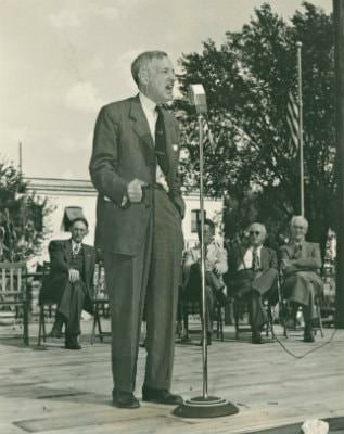 Old black and white photograph of a man standing on a platform talking passionately into a microphone