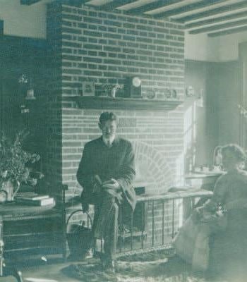 Old black and white photograph of a man and woman sitting in a sitting room near a brick fireplace