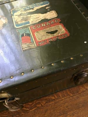 Close up view of a worn black suitcase with faded stickers from past trips
