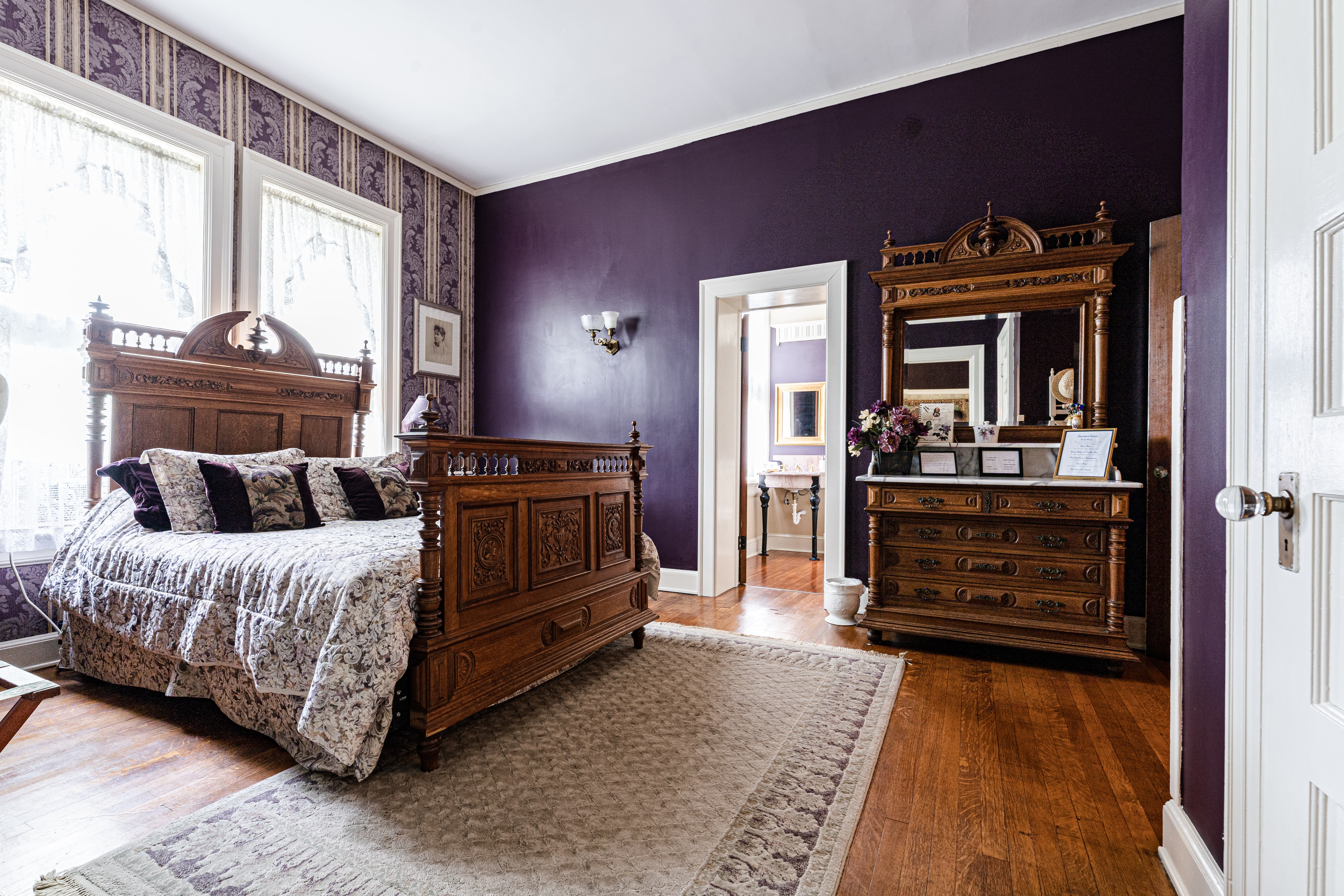 Deep purple room with white trim, white curtains, wood floors, and carved wood bed covered in floral bedding