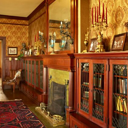 Red and gold ornate papered walls, hardwood floors with ornamental rug, and fireplace flanked by glass door covered bookcases