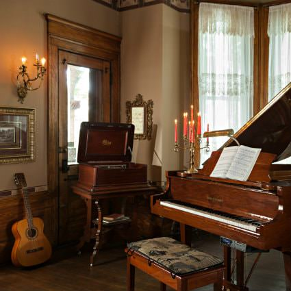 Beige room with wood floors, dark stained trim, lace curtains, a shiny wood grand piano, acoustic guitar and lit candlesticks