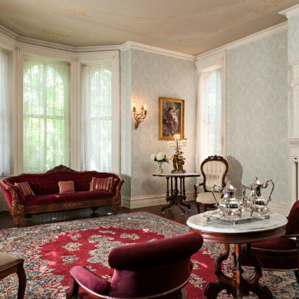 Elegant victorian room with papered walls, lace curtains, red velvet furniture, ornamental rug, and brass fixtures